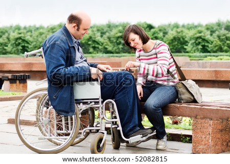 Man in wheelchair with his girlfriend - stock photo