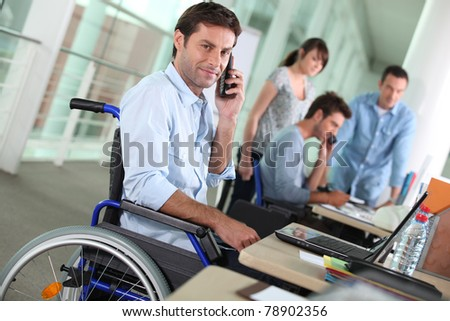Man in wheelchair with mobile phone at work - stock photo