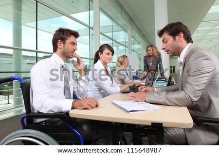Man in wheelchair working in an office - stock photo
