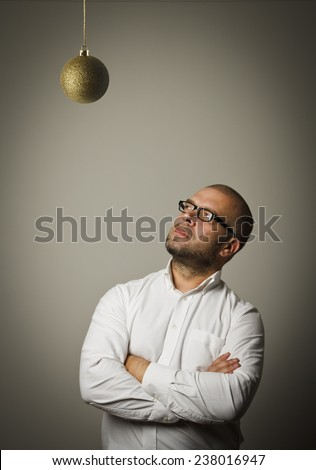 Man in white and Christmas ball which is above his head. Waiting of Christmas and New Year.  - stock photo