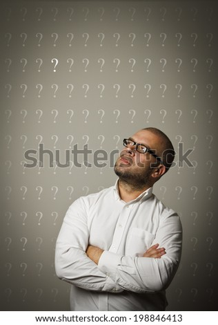 Man in white and question marks above head.  - stock photo