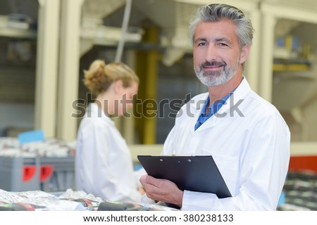 Man in white coat holding clipboard - stock photo