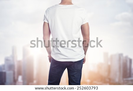 Man in white t-shirt on blurred city background - stock photo