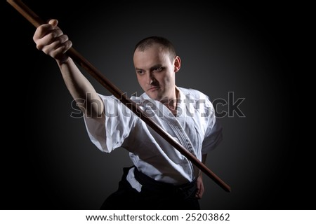 Man in white with wooden sword - stock photo