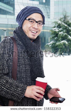 Man in winter clothes holding coffee cup and mobile phone - stock photo