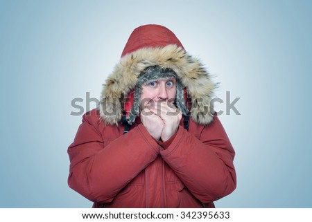 Man in winter clothes warming hands, cold, winter - stock photo