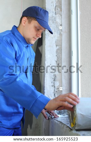 Man in working clothes places the foiled insulation on the window sill - stock photo