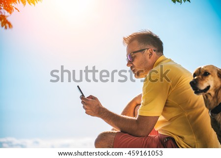 Man in yellow shirt and sunglasses using smart phone, beside him is a small yellow dog - stock photo