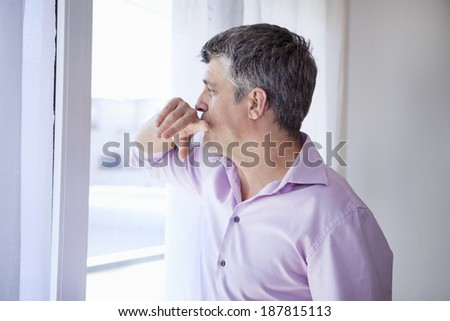 Man Indoors looking out window  - stock photo