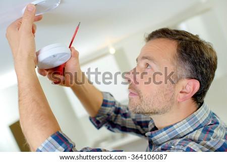 Man installing a smoke alarm - stock photo