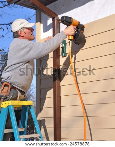 Man installing fibrous cement siding with nail gun - stock photo