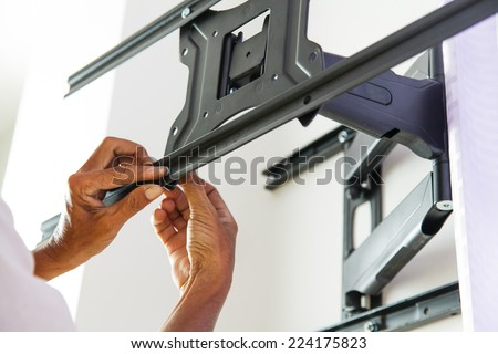 Man installing mount TV on the wall at home - stock photo