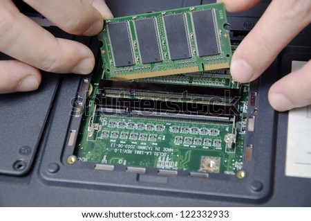 Man installing new ram for laptop - stock photo