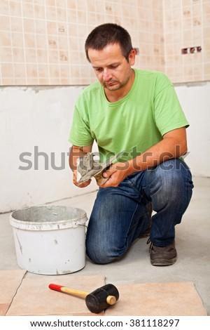 Man installs ceramic floor tiles - preparing to apply the adhesive - stock photo