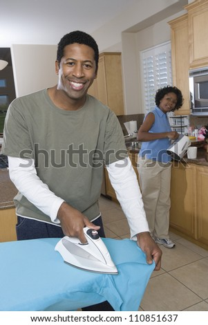 Man ironing his shirt in the kitchen - stock photo