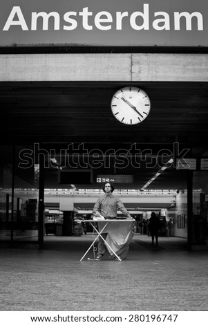 Man ironing his suit in the city on the platform in front of a train station, Amsterdam, Netherlands - stock photo