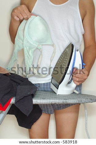man ironing holding a bra 2 - stock photo