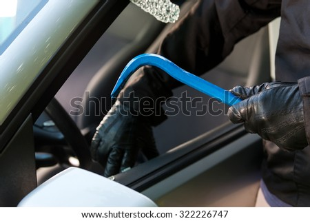 Man is a black mask trying to steal a parking car at daytime. - stock photo