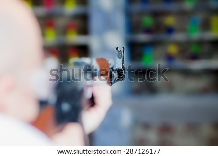 Man is aiming a gun in the shooting-range. Sight is close-up - stock photo