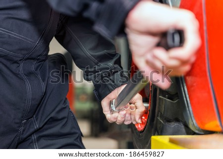Man is changing the tyre of a forklift in the maintenance area. - stock photo