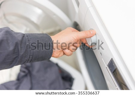 Man is choosing Eco Program on the Washing Machine,concept of electricity savings - stock photo