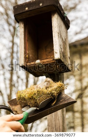 man is cleaning a birdhouse with a shovel - stock photo