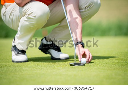 Man is concentrating to hit the golf ball on the putting green with his golf club. Trying to find out the best way to hit it. - stock photo