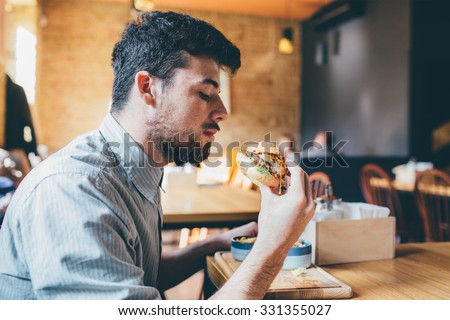 Man is eating in a restaurant and enjoying delicious food  - stock photo