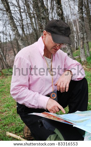 Man is examining the terrestrial map. The compass is hung on his neck. He is getting his bearings. - stock photo