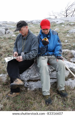 Man is examining the terrestrial map. The compass is hung on his neck. Teenage boy is orienteering by GPS. They are finding their bearings on the ground. Both hikers are sitting on a rock. - stock photo