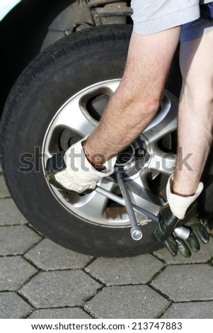 man is fixing a flat tire on car - stock photo