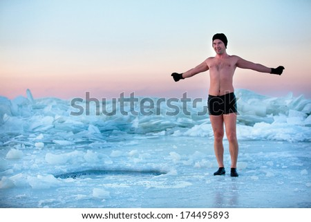 Man is going to swimm in an ice-hole - stock photo