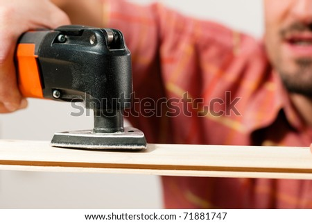 Man is grinding a plank in his house; presumably he is renovating - stock photo