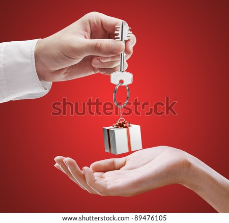 Man is handing a house key to a woman. Key with a keychain in the shape of the gift box. House key on a red background. - stock photo