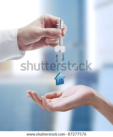 Man is handing a house key to a woman.Key with a keychain in the shape of the house. - stock photo