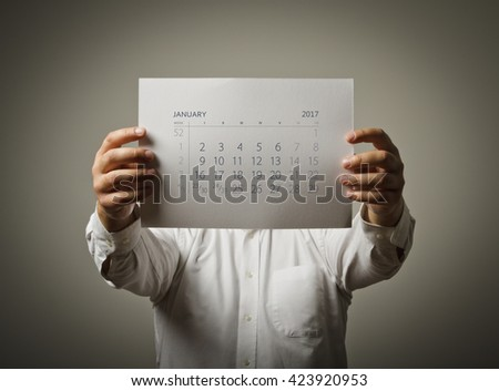 Man is holding January calendar of the year two thousand seventeen. - stock photo