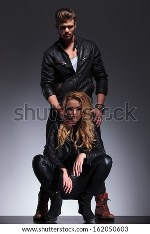 man is holding the head of his girlfriend while she is standing crouched on gray background - stock photo
