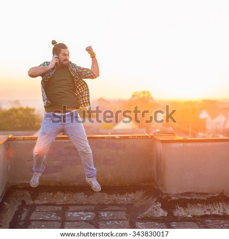 Man is jumping in the air on the top of the building and talking on his smart phone. Shallow depth of field. - stock photo