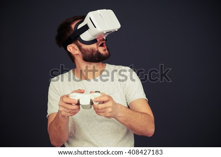 Man is playing on the joystick and looking up in virtual reality, on black background - stock photo