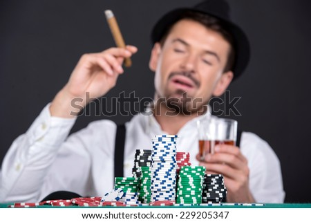 Man is playing poker in casino.With hat, cigar and a glass of whiskey. - stock photo