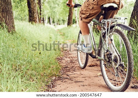 Man is riding bicycle on path in summer park, face is not visible - stock photo