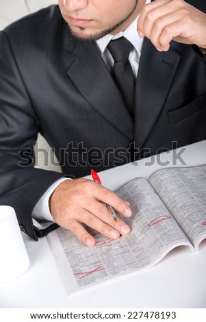 Man is searching for a job in the paper. Isolated, close-up. - stock photo