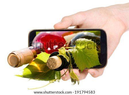 Man is showing 3d photo with wine bottles on smart mobile phone - stock photo
