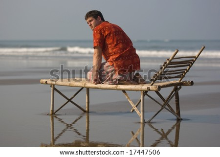 man is siting on the trestle-bed - stock photo