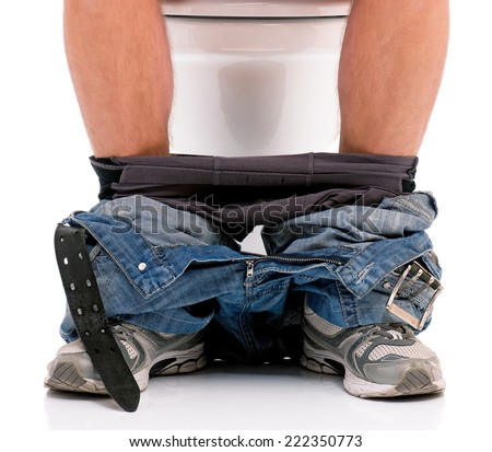 Man is sitting on the toilet bowl - stock photo