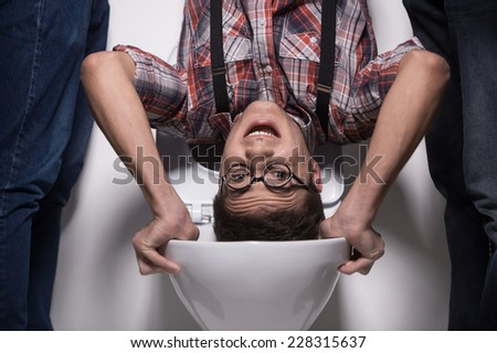 man is standing upside down on toilet bowl. closeup on two man holding man over toilet seat - stock photo