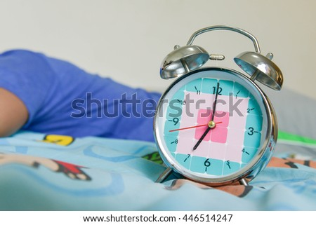 Man is still sleeping on the bed with Alarm clock is showing time for 7 AM - stock photo