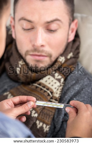 Man is suffering from cold. The woman cares about her, check temperature. - stock photo