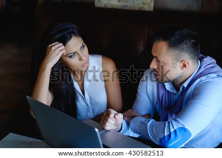 Man is talking and his colleague is listening in front of the computer - stock photo