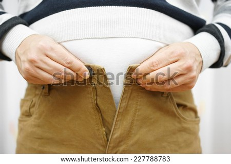 man is unable to close his pants because of gaining weight - stock photo
